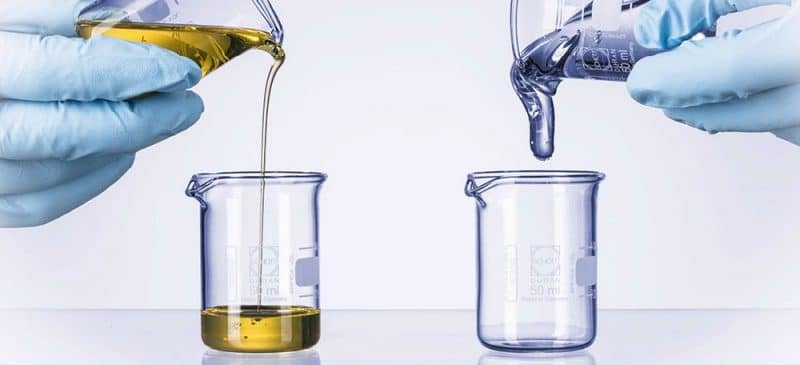 image showing two liquids with differing viscosity being poured out of beakers.